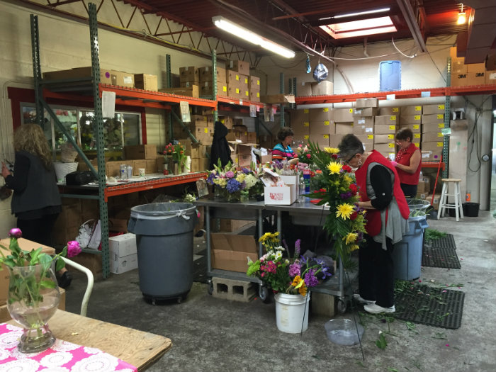 Workers arrange bouquets for a Goquets regional partner and Des Moines-area florist Boesen The Florist.