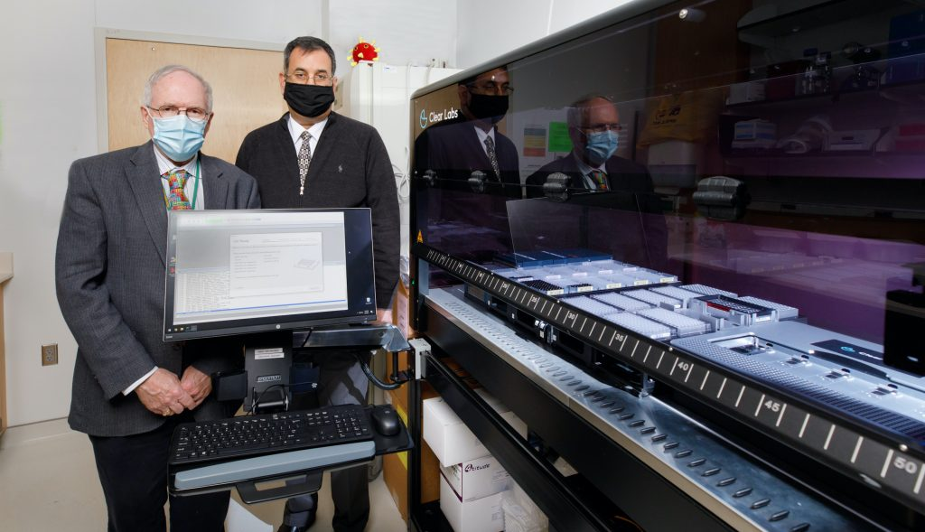 Peter Iwen, PhD,  left, & Abdalhamid Baha, MD, PhD, with  Clear Labs GridIron sequencer.